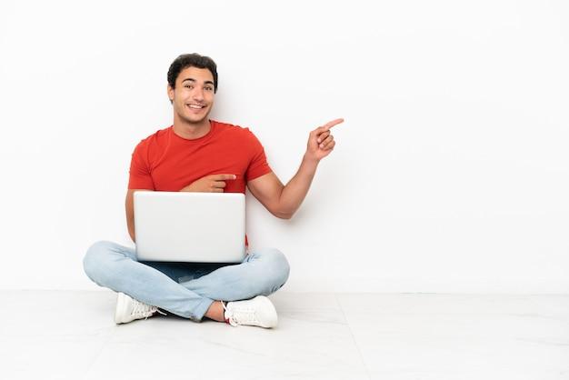 Blanke knappe man met een laptop die op de grond zit en met de vinger naar de zijkant wijst