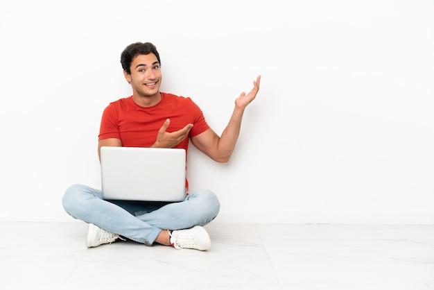 Blanke knappe man met een laptop die op de grond zit en zijn handen naar de zijkant uitstrekt om uit te nodigen om te komen
