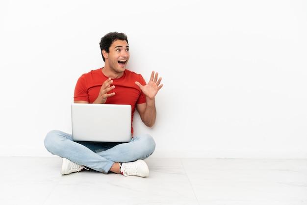 Blanke knappe man met een laptop die op de grond zit met een verbaasde gezichtsuitdrukking