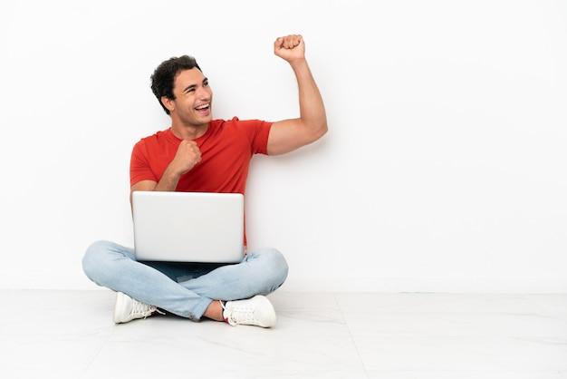 Blanke knappe man met een laptop die op de vloer zit en een overwinning viert