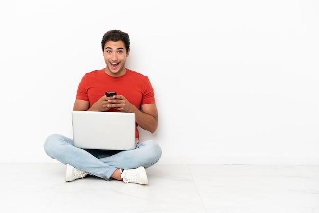 Blanke knappe man met een laptop die verrast op de grond zit en een bericht stuurt