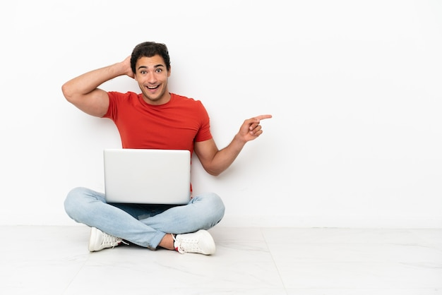 Blanke knappe man met een laptop die verrast op de grond zit en met de vinger naar de zijkant wijst