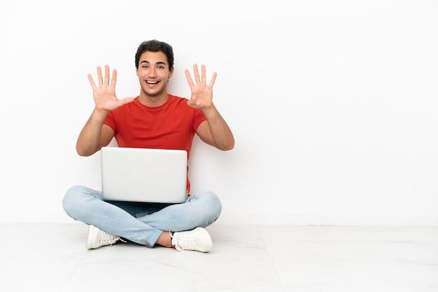 Blanke knappe man met een laptop op de grond die negen telt met vingers