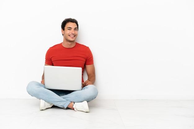 Blanke knappe man met een laptop zittend op de vloer met gekruiste armen en vooruitkijkend