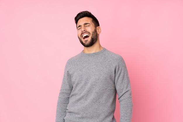 Blanke knappe man over geïsoleerde muur lachen