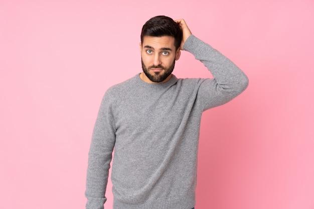 Blanke knappe man over geïsoleerde muur met een uitdrukking van frustratie en niet begripvol