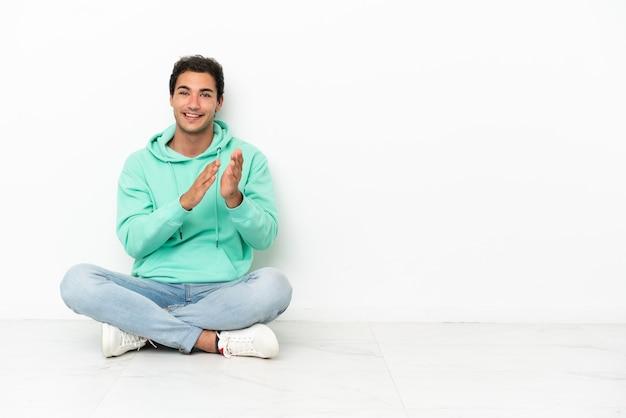 Blanke knappe man zittend op de vloer applaudisserend na presentatie in een conferentie