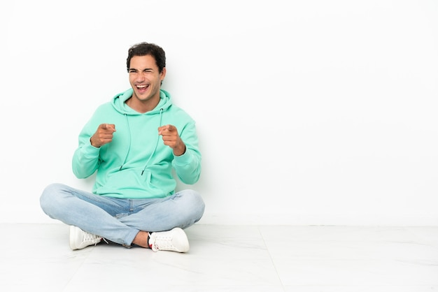 Blanke knappe man zittend op de vloer naar voren wijzend en glimlachend