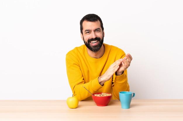 Blanke man aan het ontbijt in een tafel applaudisseren