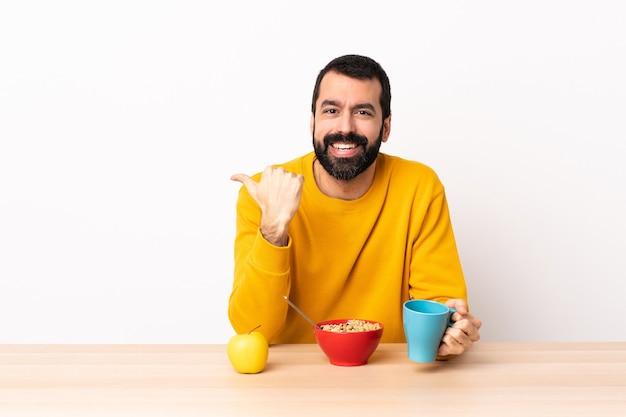 Blanke man aan het ontbijten in een tafel die naar de zijkant wijst om een product te presenteren.