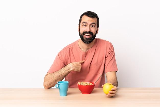 Blanke man aan het ontbijten in een tafel met een verrassende gezichtsuitdrukking.