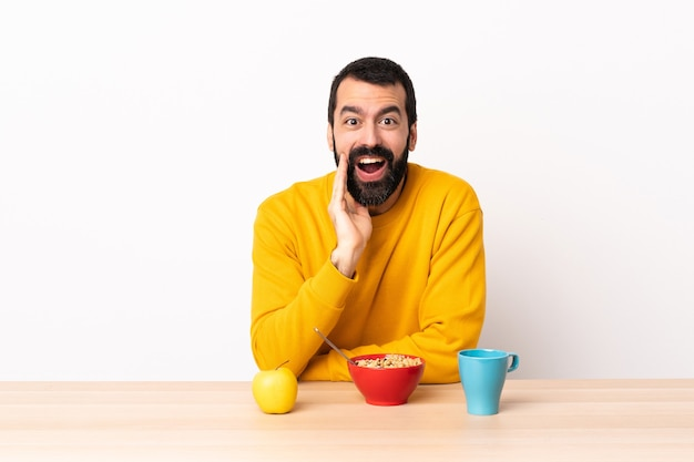 Blanke man aan het ontbijten in een tafel met verbazing en geschokt gelaatsuitdrukking.