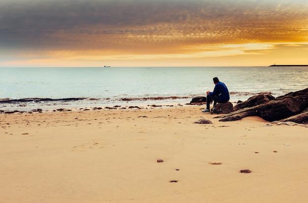Blanke man alleen zittend op de oever van de zee