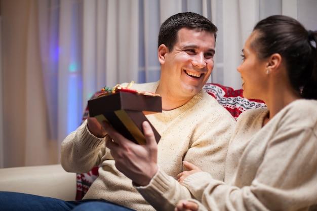 Blanke man blij met zijn geschenk op eerste kerstdag van zijn vrouw.