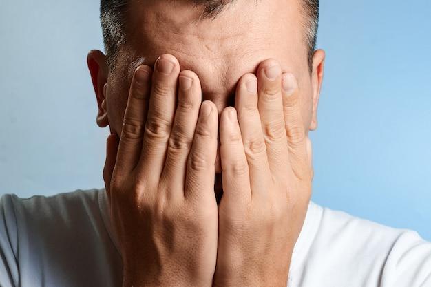 Blanke man, close-up portret, bedekte zijn gezicht met zijn handen op blauw