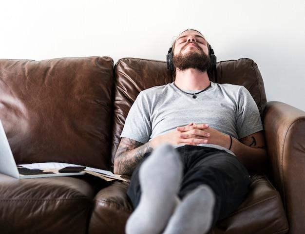 Blanke man die een pauze van het werk door te luisteren naar muziek