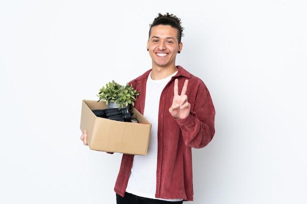 Blanke man die een zet doet terwijl het oppakken van een doos vol dingen over geïsoleerde witte muur glimlachend en overwinningsteken toont