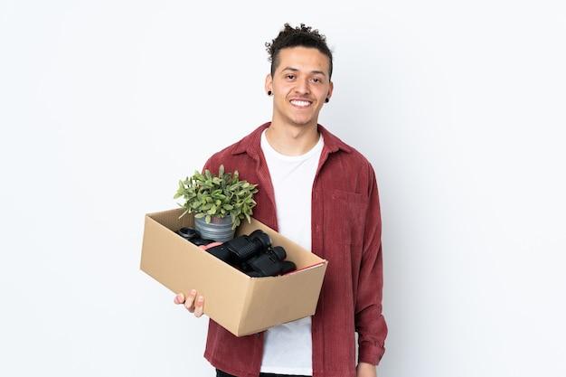 Blanke man die een zet doet terwijl hij een doos vol dingen oppakt over geïsoleerde witte muur die veel glimlacht