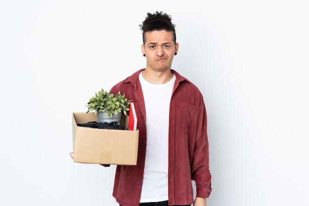 Blanke man die een zet doet terwijl hij een doos vol dingen oppakt over geïsoleerde witte muur met droevige uitdrukking
