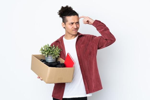 Blanke man die een zet doet terwijl hij een doos vol dingen oppakt over geïsoleerde witte muur met twijfels en met een verwarde gezichtsuitdrukking