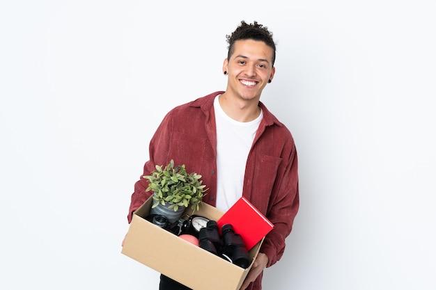 Blanke man die een zet doet terwijl hij een doos vol dingen oppakt over geïsoleerde witte muur