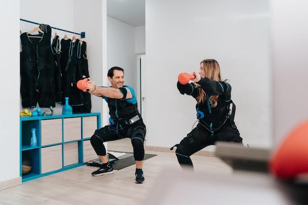 Blanke man doet push-ups aan een touw terwijl hij een elektrostimulatie draagt