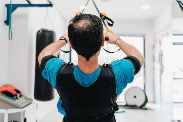 Blanke man doet push-ups aan een touw terwijl hij een elektrostimulatiepak draagt