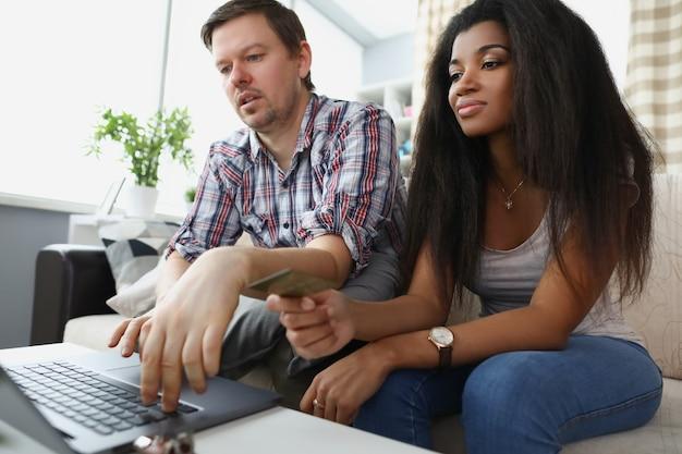Blanke man en afro-amerikaanse vrouw zitten thuis achter laptopscherm screen