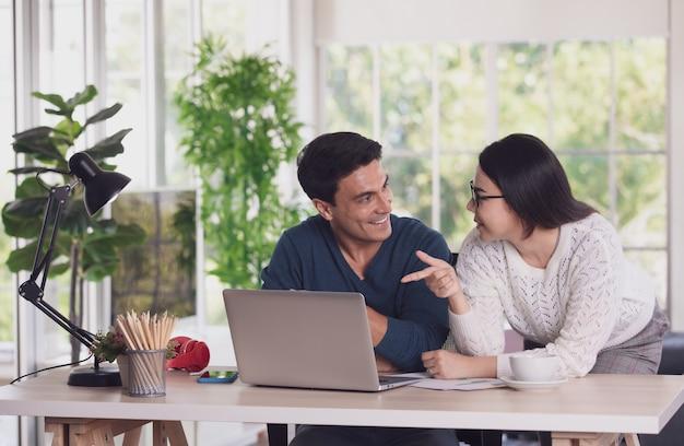 Blanke man en aziatische vrouw mixen raceliefhebbers die samenwerken via een laptop-notebookcomputer en in de woonkamer discussiëren met gelukkig en intiem. nieuw normaal werk op kantoor aan huis concept.