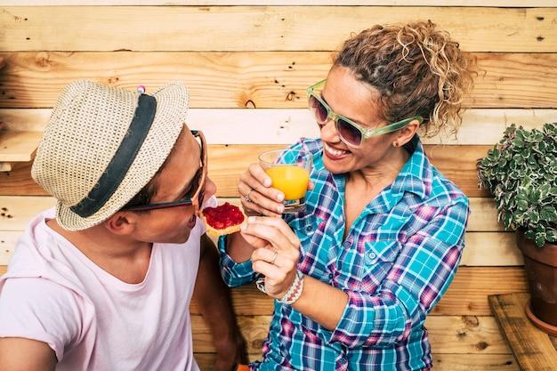 Blanke man en volwassen vrouw thuis op het terras ontbijten samen met een grappig gezicht van de tiener terwijl hij een brood met marmelade eet - jongen met zonnebril die plezier heeft en een grapje maakt