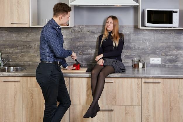 Blanke man en vrouw 22 jaar oud praten in de keuken.