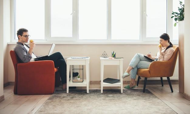Blanke man en zijn vrouw die appel eten terwijl ze in een fauteuil liggen en aan een aantal zakelijke deals werken
