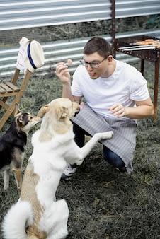 Blanke man geeft een snack aan zijn hond, buiten wandelend in de achtertuin