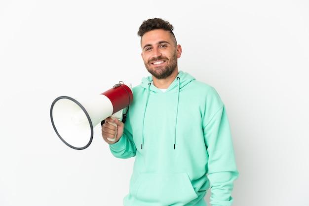 Blanke man geïsoleerd op een witte achtergrond die een megafoon vasthoudt en veel lacht