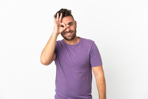 Blanke man geïsoleerd op een witte achtergrond met ok teken met vingers