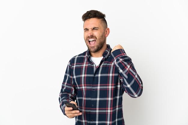 Blanke man geïsoleerd op een witte achtergrond met telefoon in overwinning positie