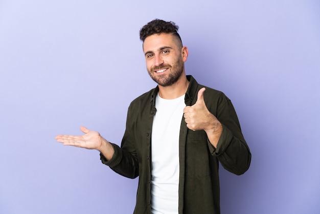 Blanke man geïsoleerd op paarse achtergrond met copyspace denkbeeldig op de palm om een advertentie in te voegen en met duimen omhoog