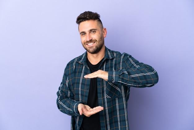 Blanke man geïsoleerd op paarse achtergrond met copyspace denkbeeldig op de palm om een advertentie in te voegen