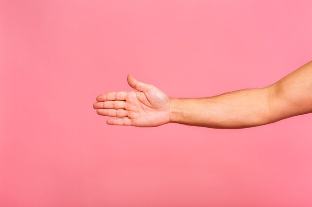 Blanke man hand opknoping iets leeg geïsoleerd op een roze.
