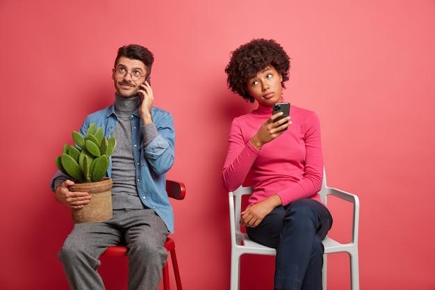 Blanke man heeft telefoongesprek houdt pot met cactus en poseert thuis op de stoel. verveelde vrouw met donkere huid houdt cellulair vast en bedenkt welk antwoord ze moet geven. mensen en moderne technologieën