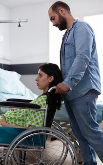 Blanke man helpt vrouw met zwangerschap in rolstoel