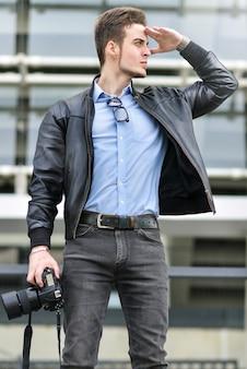 Blanke man houdt een fotocamera vast en maakt foto's.