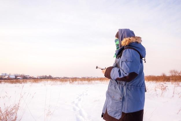 Blanke man in de blauwe jas lanceert een vliegende drone met een afstandsbediening in zijn hand op winterveld.