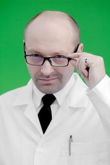 Blanke man in een witte laboratoriumjas, bril, op een groene achtergrond