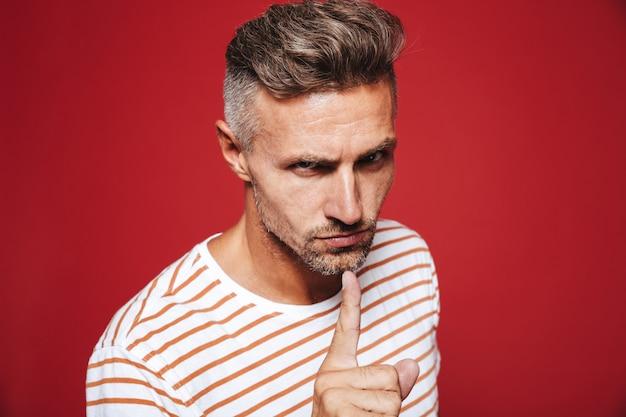 Blanke man in gestreept t-shirt met wijsvinger op lippen met boze blik geïsoleerd op rood