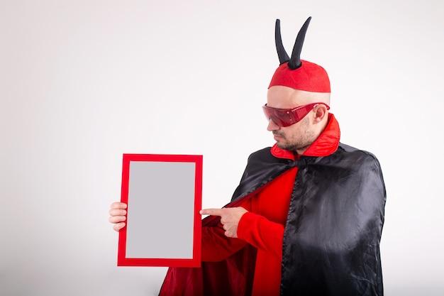 Blanke man in halloween kostuum leeg naamplaatje demonstreren op witte studio achtergrond.