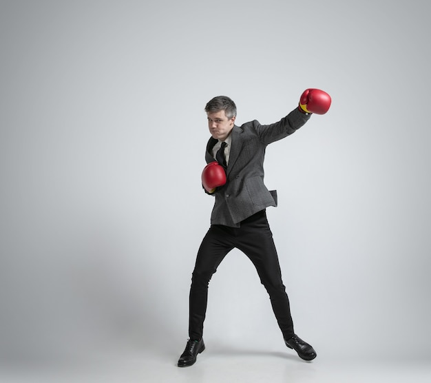 Blanke man in het boksen van kantoorkleren geïsoleerd op een grijze muur