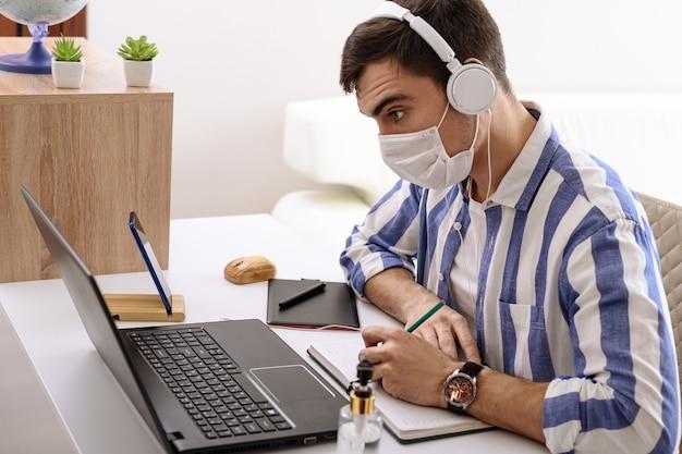 Blanke man in masker en koptelefoon luistert naar muziek, schrijft in notitieblok, externe werk thuis