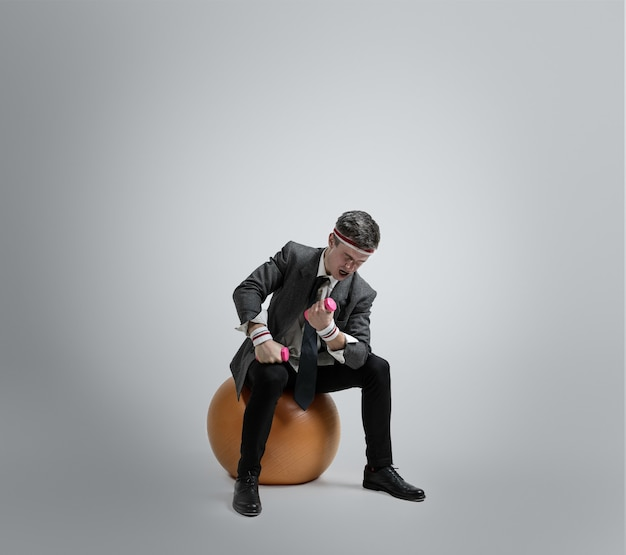 Blanke man in office kleding opleiding geïsoleerd op grijze studio achtergrond