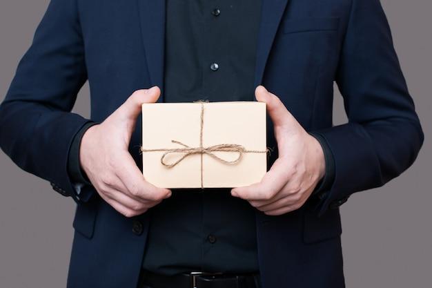 Blanke man in pak houdt een cadeautje in handen poseren zonder gezicht op een grijze muur met vrije ruimte